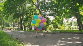 愉快,嬉戏的女孩摆在与在步行的五颜六色的气球在晴朗的公园 影视素材