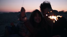 愉快,微笑的三口之家加速的英尺长度坐在与闪烁发光物的篝火附近的海滩的户外 影视素材