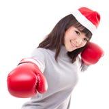 愉快,微笑的妇女佩带的圣诞节圣诞老人帽子,拳击手套, 免版税库存图片