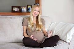 愉快,微笑的孕妇坐有杯的长沙发水 库存照片