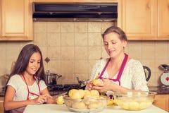 愉快,微笑的烹调晚餐的母亲和女儿 免版税库存照片