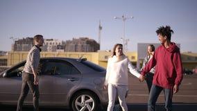 愉快,微笑的multirace年轻两对夫妇从汽车和走动出去由停车区在购物中心附近 两 股票视频