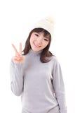 愉快,微笑,快乐的妇女佩带的编织帽子,显示2个手指 库存照片