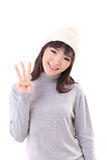 愉快,微笑,快乐的妇女佩带的编织帽子,显示3个手指 免版税库存照片