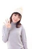 愉快,微笑,快乐的妇女佩带的编织帽子,显示4个手指 免版税库存照片