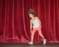 愉快,快乐的小女孩看看她的头发运动,当她跑,跳舞在夜阶段反对深红帷幕backgr时 免版税库存照片