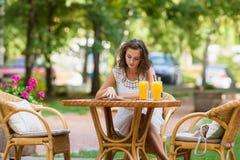 愉快,正面,美丽,坐在咖啡馆的高雅女孩制表户外 免版税库存图片