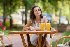 愉快,正面,美丽,坐在咖啡馆的高雅女孩制表户外 免版税图库摄影