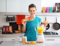 愉快,适合的妇女在准备一名健康圆滑的人的厨房里 库存照片