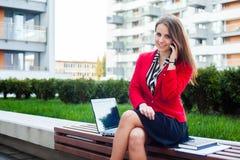 愉快年轻专业女商人坐室外与暴民 免版税库存图片