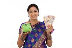 愉快年轻传统妇女举行印地安货币的和贪心 库存图片