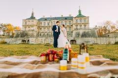 愉快结婚用香槟站立在野餐构成后和在背景哥特式 免版税库存照片