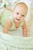 愉快婴孩的小儿床 免版税图库摄影