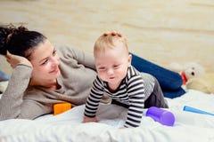愉快婴孩的背景她的演奏空白年轻人的查出的母亲 免版税图库摄影