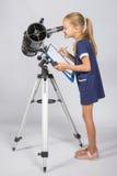 愉快年轻的天文学家通过望远镜录音观察看 免版税库存图片