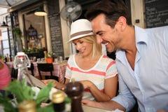 愉快年轻的夫妇品尝意大利食物 免版税库存图片