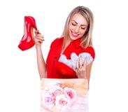 愉快年轻美丽的妇女接受红色高跟鞋鞋子和负担作为礼物 免版税库存照片