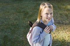 愉快bookbag基本的女孩她的学校 免版税库存照片