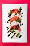 意大利人Caprese沙拉用无盐干酪蕃茄牛至黑胡椒和香醋在白色板材在红色背景 免版税图库摄影