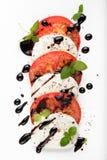 意大利人Caprese沙拉用无盐干酪蕃茄牛至黑胡椒和香醋在白色板材 库存照片