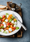 意大利人Caprese沙拉用西红柿、小无盐干酪和新鲜的蓬蒿 免版税图库摄影