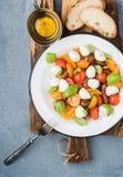 意大利人Caprese沙拉用西红柿、小无盐干酪和新鲜的蓬蒿 库存图片