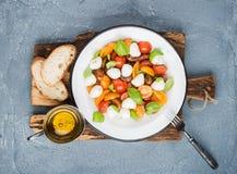 意大利人Caprese沙拉用西红柿、小无盐干酪和新鲜的蓬蒿 免版税库存图片