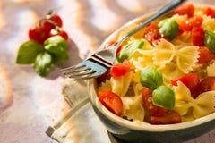 意大利人Farfalle面团特写镜头用蕃茄、蓬蒿和叉子 免版税库存照片