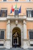 意大利卡宾抢手警察在一个历史建筑的一个公开机关守卫入口在有意大利a的旗子的罗马 库存照片