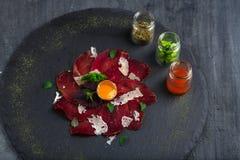 意大利可口开胃小菜bresaola用牛至,鹌鹑蛋,在石板材,顶视图的葱 图库摄影