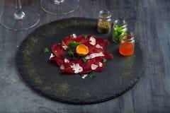 意大利可口开胃小菜bresaola用牛至,鹌鹑蛋,在石板材,顶视图的葱 免版税库存图片