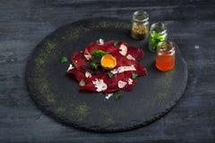 意大利可口开胃小菜bresaola用牛至,鹌鹑蛋,在石板材,顶视图的葱 库存照片