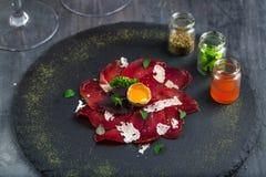 意大利可口开胃小菜bresaola用牛至,鹌鹑蛋,在石板材,顶视图的葱 免版税库存照片