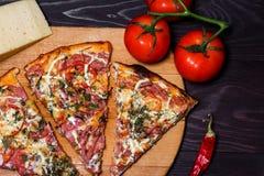 意大利土气比萨,三个片断在一个木盘子,黑暗的木桌,用蕃茄、乳酪和辣椒 免版税库存照片