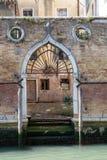 意大利威尼斯 一条运河的老被成拱形的水门在一个被风化的砖墙 免版税库存图片
