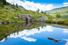 意大利山全景,云彩在高山湖反射了 图库摄影