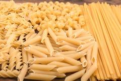意大利干面团各种各样的类型和形状在木背景的 未煮过,坚硬,未加工和干面团 干鲜美通心面 图库摄影
