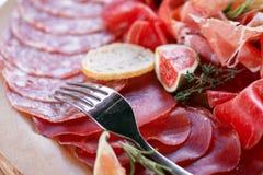意大利开胃小菜和开胃菜 上与切片熏火腿,蒜味咸腊肠,干猪肉,蒜味咸腊肠火腿用草本 库存照片