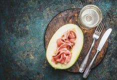 意大利开胃小菜用火腿、瓜和酒服务与在土气背景的利器 免版税库存图片