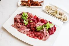 意大利开胃小菜盛肉盘冷的开胃小菜肉板材朝鲜蓟各式各样的蕃茄 图库摄影