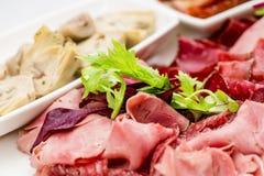 意大利开胃小菜盛肉盘冷的开胃小菜肉板材朝鲜蓟各式各样的蕃茄 库存图片