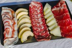 意大利开胃小菜盛肉盘蒜味咸腊肠、火腿、pancetta、梨和瓜 免版税库存照片