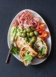 意大利开胃小菜-熏火腿,橄榄,西红柿,无盐干酪菠菜在黑暗的背景的ciabatta三明治 免版税库存照片