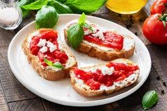 意大利开胃小菜bruschetta用烤胡椒、橄榄油和山羊乳干酪或者希腊白软干酪 免版税库存图片