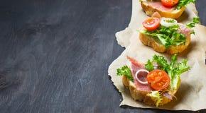 意大利开胃小菜crostini用火腿、沙拉和蕃茄 图库摄影