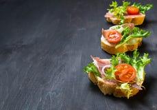 意大利开胃小菜crostini用火腿、沙拉和蕃茄 免版税图库摄影