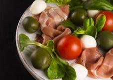 意大利开胃菜:熏火腿、无盐干酪、西红柿、莴苣和橄榄在黑木背景 免版税库存图片