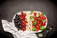 意大利开胃菜-无盐干酪、蕃茄、橄榄和蓬蒿 库存图片