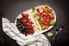 意大利开胃菜-无盐干酪、蕃茄、橄榄和蓬蒿 免版税图库摄影