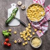 意大利式饺子用烹调在厨房用桌背景的夏南瓜和素食主义者成份与切板和刀子,顶视图 他 库存图片
